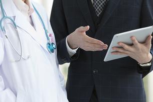 医師にタブレットPCを見せるビジネスマンの手元の写真素材 [FYI01313847]