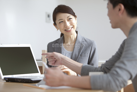 ノートパソコンを見せて説明をするビジネスウーマンの写真素材 [FYI01313867]