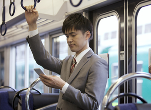 通勤電車でスマートフォンを見ているビジネスマンの写真素材 [FYI01313901]