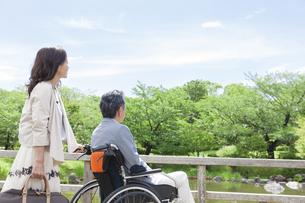 遠くを見ている車椅子の中高年男性と女性の写真素材 [FYI01313929]