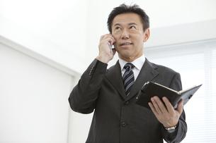 スマートフォンで電話するビジネスマンの写真素材 [FYI01314194]