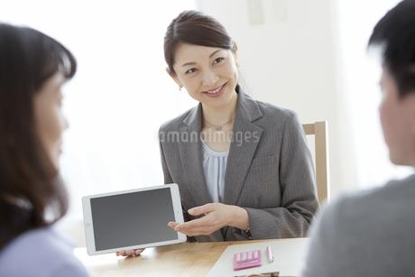 タブレットPCを見せて説明をするビジネスウーマンの写真素材 [FYI01314241]