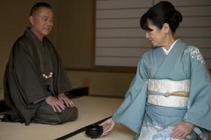 お茶を差し出す中高年女性の写真素材 [FYI01314248]
