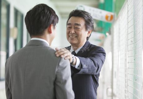 バッティングセンターで話すビジネスマン2人の写真素材 [FYI01314289]