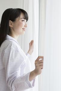 カーテンを開ける女性の写真素材 [FYI01314408]