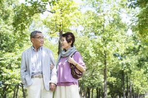 公園を歩くシニア夫婦の写真素材 [FYI01314551]
