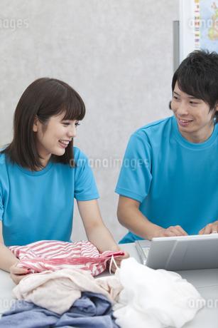 ノートパソコンを見て話す男女の写真素材 [FYI01314727]