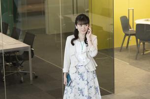 スマートフォンで通話するビジネスウーマンの写真素材 [FYI01314849]