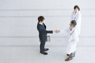 握手をするビジネスマンと医師の写真素材 [FYI01314942]