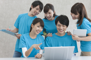 ノートパソコンを見て話す男女5人の写真素材 [FYI01314959]