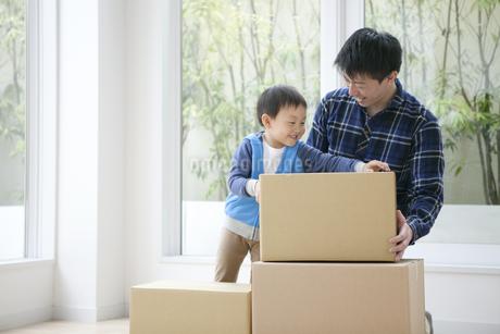 引っ越しの荷物を持つ男の子と父親の写真素材 [FYI01314966]