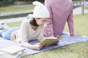 公園で本を読む女性と男性の後姿の写真素材 [FYI01315034]