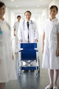 車椅子を押す男性医師と看護師3人の写真素材 [FYI01315104]