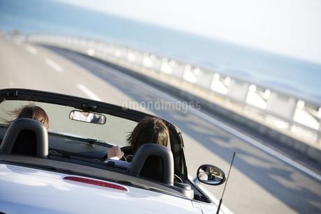 オープンカーに乗るカップルの後姿の写真素材 [FYI01315143]