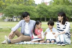 芝生に座る4人家族の写真素材 [FYI01315366]
