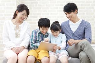 ソファーに座ってタブレットPCを見ている4人家族の写真素材 [FYI01315416]