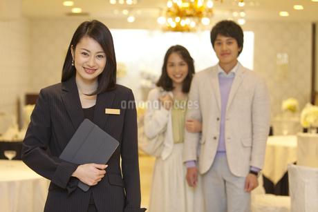 笑顔のウエディングプランナーとカップルの写真素材 [FYI01315612]