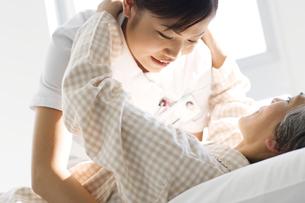 シニア女性患者を抱きかかえる介護士の写真素材 [FYI01315663]