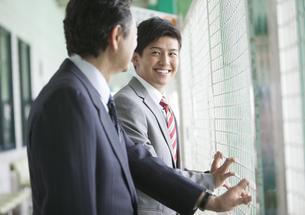 バッティングセンターで話すビジネスマン2人の写真素材 [FYI01316009]