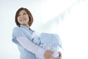 洗濯カゴを抱えている笑顔の女性の写真素材 [FYI01316020]