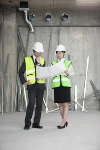 タブレットPCを見る男女の作業員の写真素材 [FYI01316037]