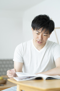 雑誌を読む男性の写真素材 [FYI01316087]