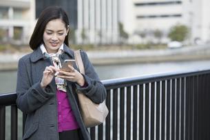 スマートフォンを操作するビジネスウーマンの写真素材 [FYI01316143]