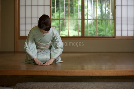 玄関で挨拶する着物姿の女性の写真素材 [FYI01316260]
