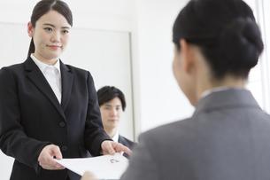 面接官に履歴書を渡す女性の写真素材 [FYI01316276]