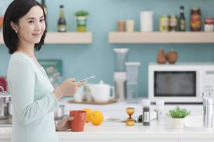 キッチンでスマートフォンを持つ女性の写真素材 [FYI01316282]