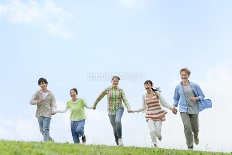 手をつないで走る若者5人の写真素材 [FYI01316299]