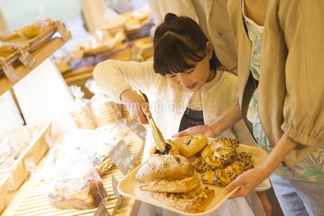 パンをトレイにのせる女の子の写真素材 [FYI01316388]