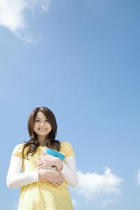 本を持っている笑顔の女性の写真素材 [FYI01316476]
