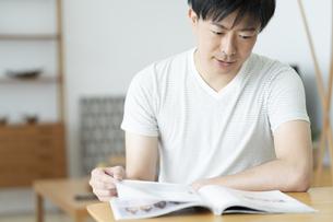 雑誌を読む男性の写真素材 [FYI01316501]
