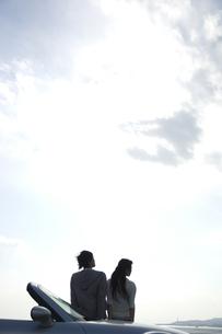 ボンネットに腰掛けるカップルの写真素材 [FYI01316533]