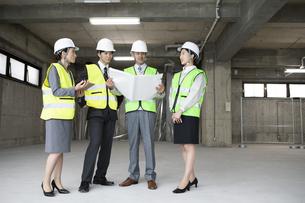建設現場で図面を広げるビジネス男女の写真素材 [FYI01316644]