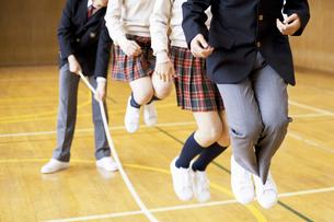 体育館で大縄跳びをする学生達の写真素材 [FYI01316660]