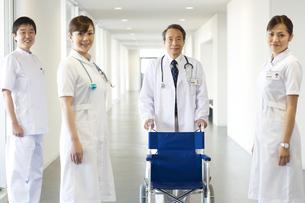 車椅子を押す男性医師と看護師3人の写真素材 [FYI01316896]
