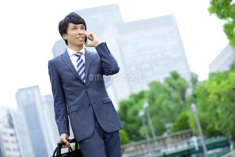 スマートフォンで電話をするビジネスマンの写真素材 [FYI01316919]