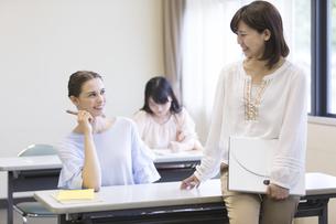 教室で話している女子大生の写真素材 [FYI01316988]