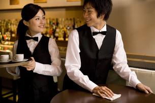 仕事をしながら話す女性従業員と男性従業員の写真素材 [FYI01316993]