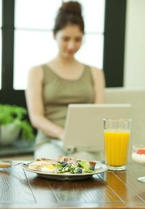 朝食とパソコンを操作する女性の写真素材 [FYI01317142]