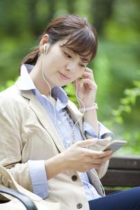スマートフォンで音楽を聴くビジネス女性の写真素材 [FYI01317148]