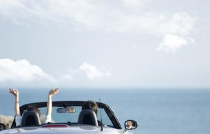 オープンカーに乗るカップルの後姿の写真素材 [FYI01317172]