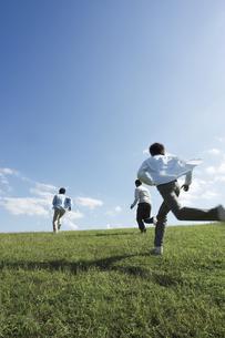 草原を走る若い男性3人の写真素材 [FYI01317284]