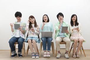 電子機器を操作する若者5人の写真素材 [FYI01317484]