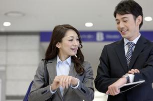 腕時計を見るビジネスマンとビジネスウーマンの写真素材 [FYI01317531]