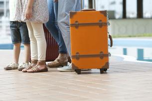旅行かばんと4人家族の足元の写真素材 [FYI01317701]