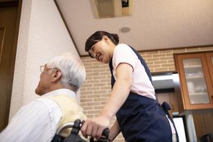 車椅子に乗るシニア男性とヘルパーの写真素材 [FYI01317751]