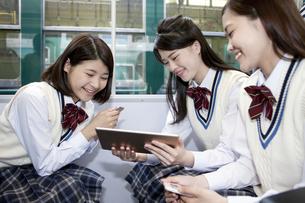 電車でタブレットPCを見ている女子高生の写真素材 [FYI01317770]